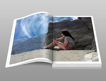 Photo of open book page displaying woman sitting near brown rock during day time
