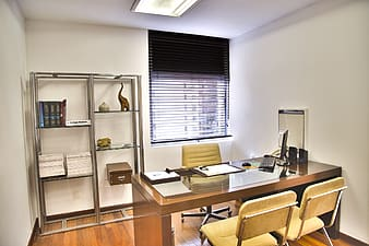 Brown wooden executive desk and two vacant chairs