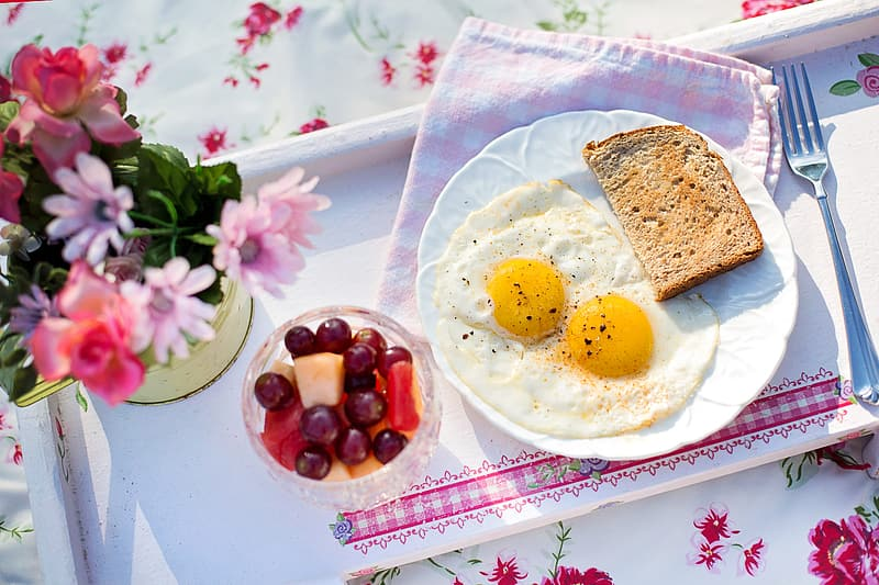 Fried egg and sliced bread on plate beside cup of fruits