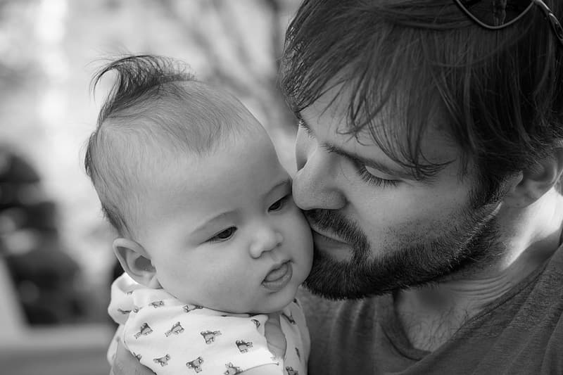 Grayscale photography of man kissing baby