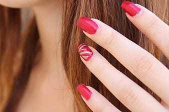 Close up view of women's red polished fingernails