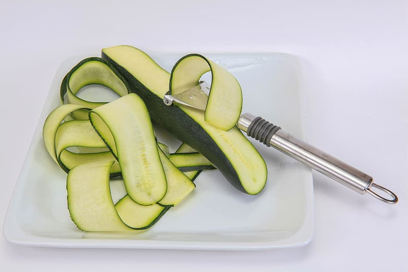 Silver kitchen utensil peeling cucumber