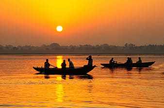 Silhouette photo of people riding boat during golden hour