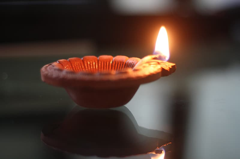 Lit candle on brown holder
