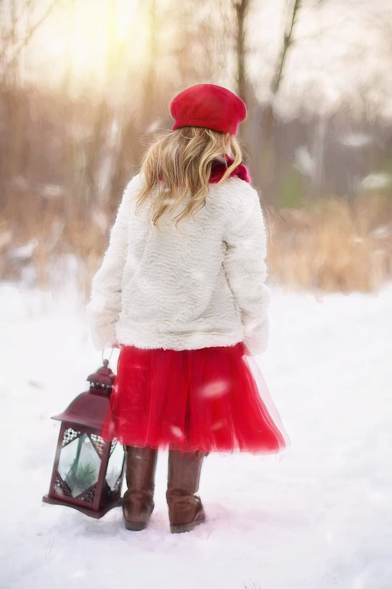 Girl in white cardigan and red dress holding lantern standing on snow field during daytime