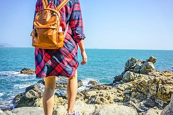 Woman wearing backpack standing beside stone near at water