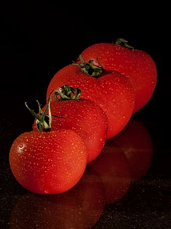 Closeup photo of four red tomatoes