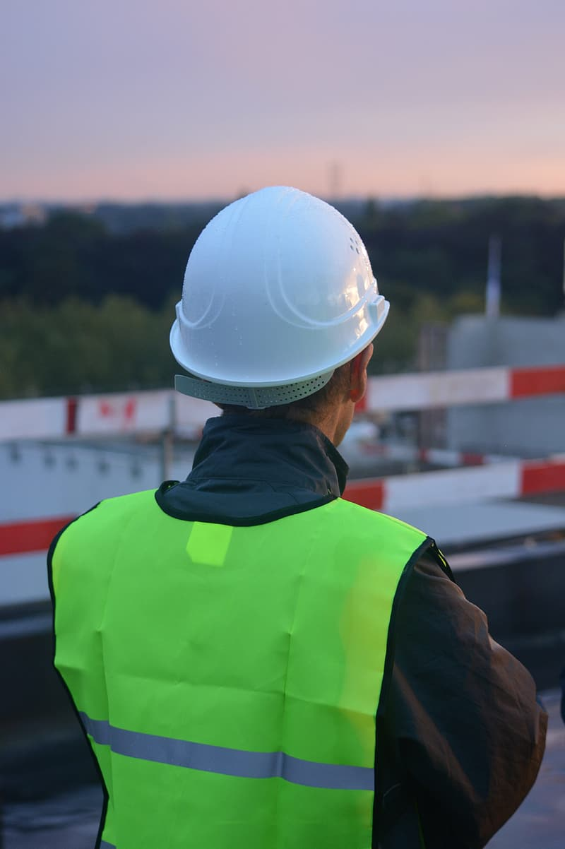 Man in green high-visibility vest with white hard hat