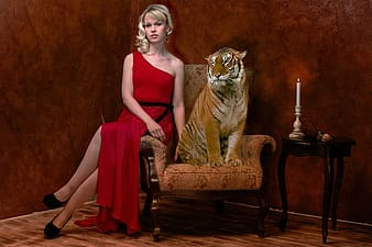 Woman in red sleeveless dress sitting on brown armchair beside tiger figurine