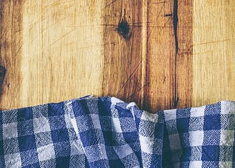 Blue and white gingham textile on brown wooden surface