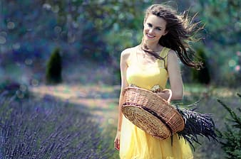Woman in yellow sleeveless dress carrying brown basket