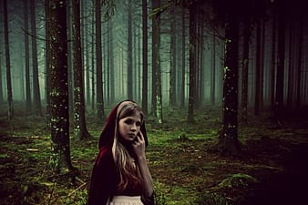 Woman wearing red cloak standing in middle of forest