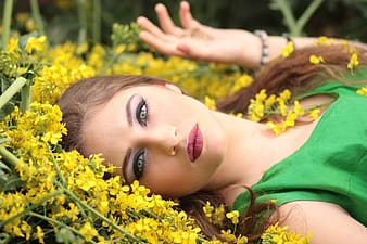 Woman lying on yellow petaled flowers wearing green sleeveless dress