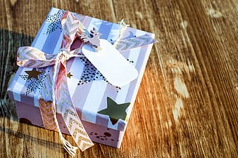 White and pink gift box on brown wooden surface