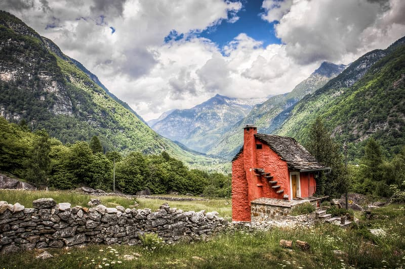 Red and black brick house surrounded by mountains
