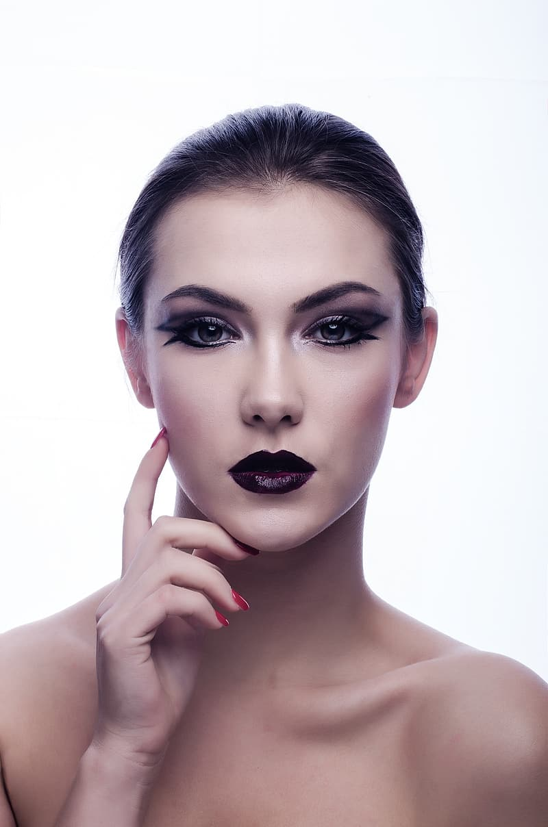 Woman wearing black lipstick, black eyeshadow, and black mascara posing in front of white background