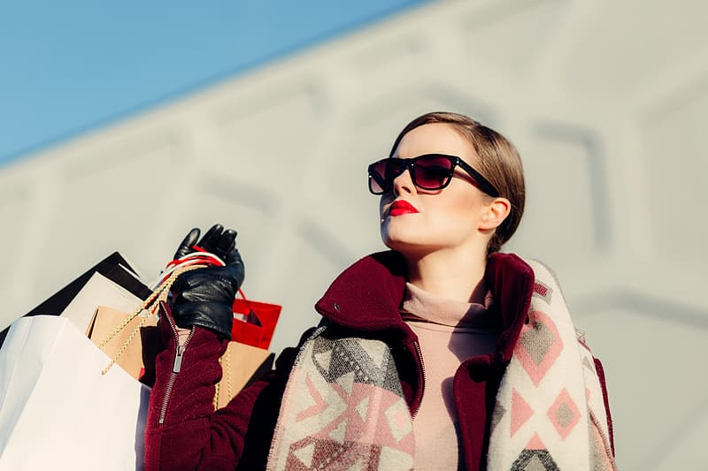 Depth of field photography of woman wearing scarf carrying paperbags