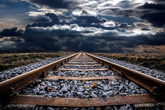 Brown metal train rail under white clouds and blue sky during daytime