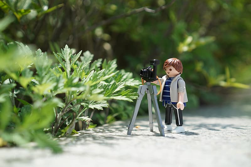 Boy plastic toy with tripod camera beside green plant at daytime