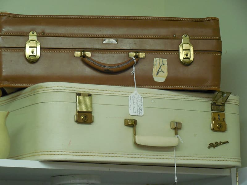 Two white and brown leather luggage on white shelf