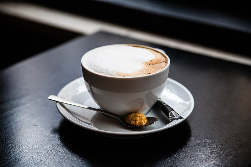 Cup of latte on saucer with gray spoon