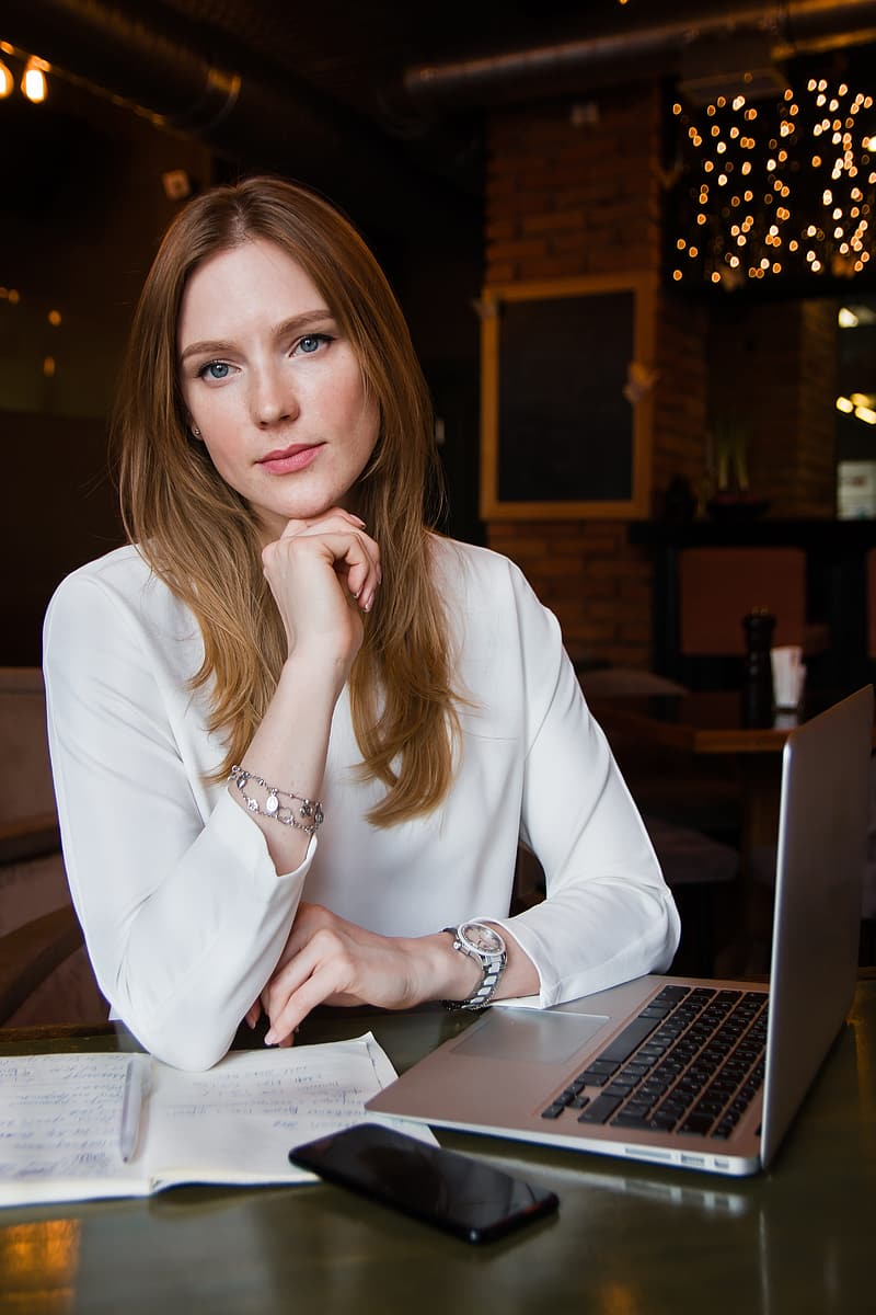 Woman in white blazer sitting by the table using macbook pro