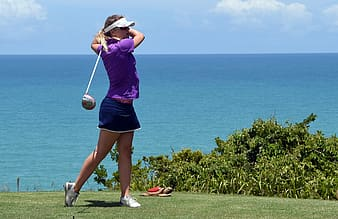 Woman in purple shirt and black mini skirt playing golf during daytime