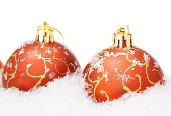 Red and green baubles on snow