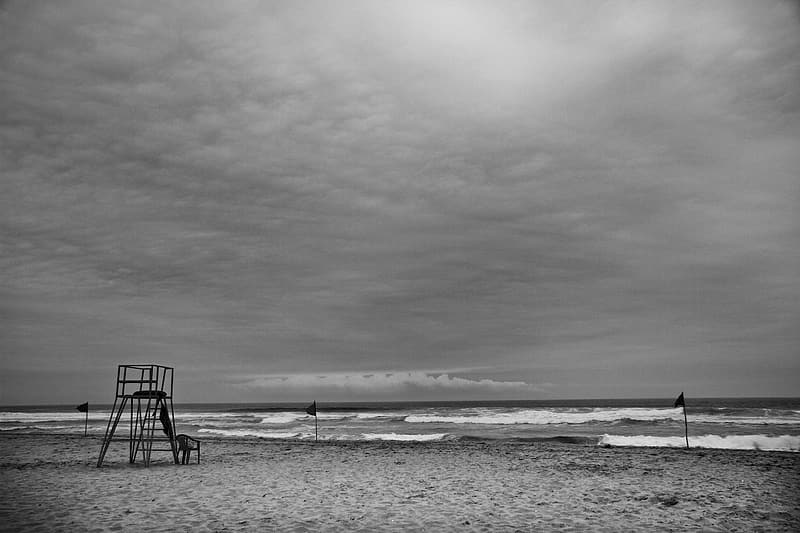 Grayscale photo of beach with wooden chair on the beach