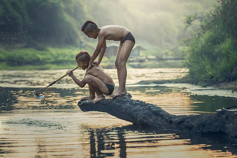 Photo of two boys standing on rock on top of body of water