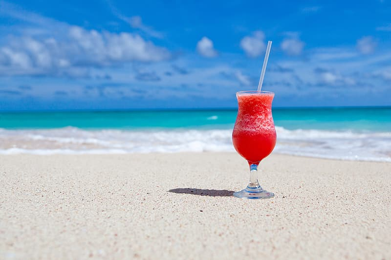 Red and black glass vase, clear footed glass cup filled with smoothie on seashore