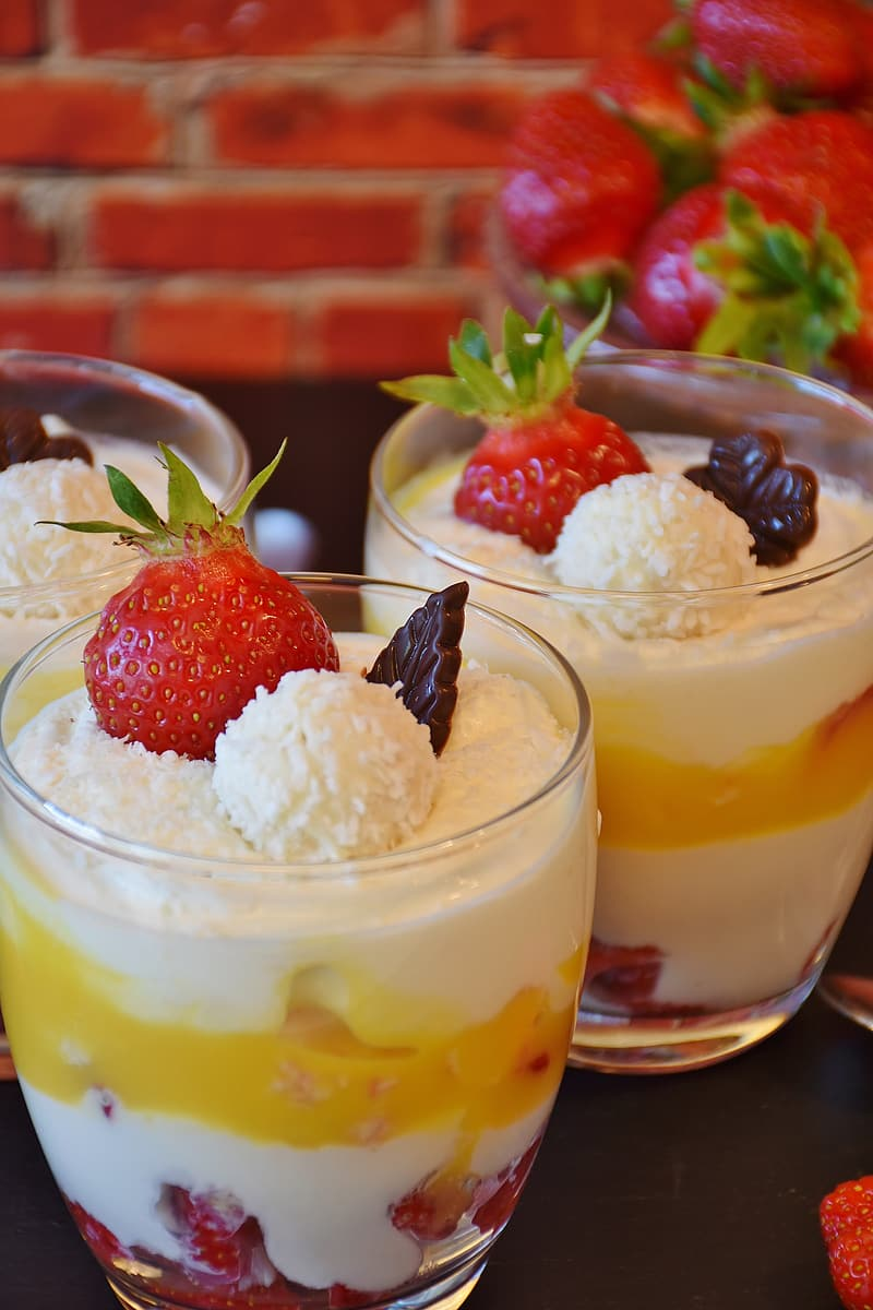 Strawberry and mango with cream and chocolate in clear glasses