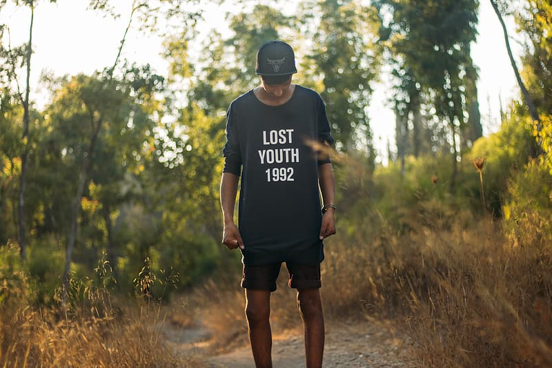 Man in black lost youth 1992-printed crew-neck sweater standing between brown grass during daytim
