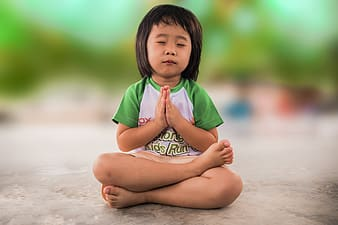 Girl wearing white and green shirt sitting while praying on grey concrete floor