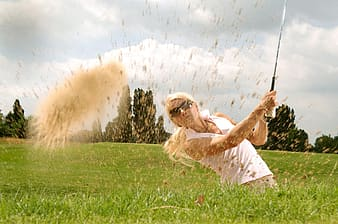 Photograph of woman holding golf driver in green grass field