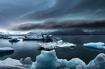 Ice formation on body of water under cloudy sky