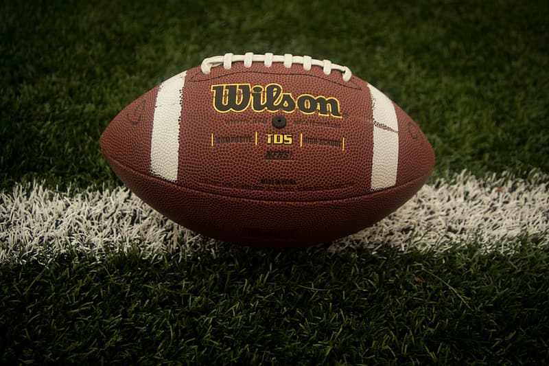 Brown and white Wilson football on grass field