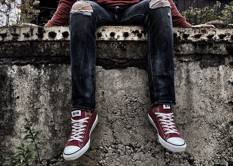 Person in blue denim jeans and red converse all star high top sneakers sitting on brown