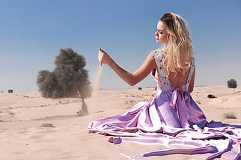Woman wearing purple dress playing with sand
