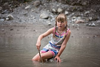 Girl sitting on rock in water
