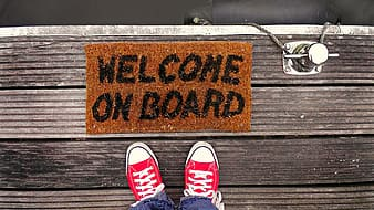Person standing beside welcome on board rug