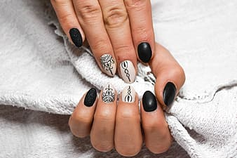 Person's hand with black and white nail polish