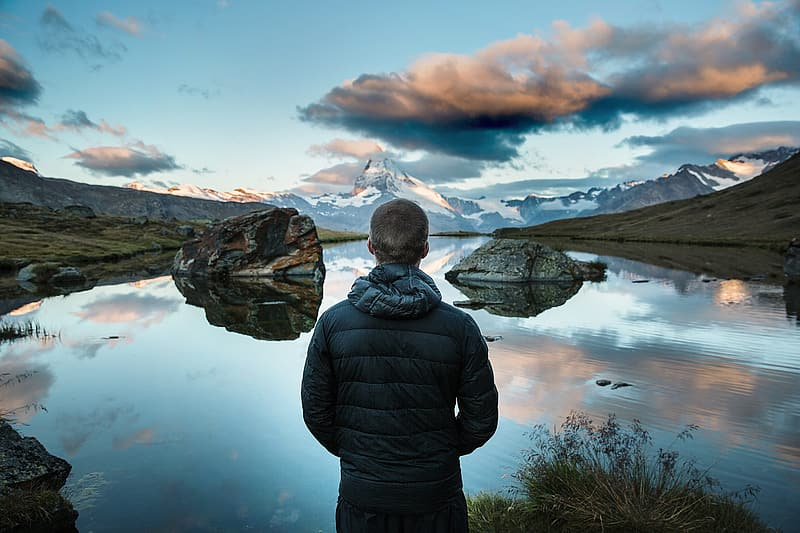 Man in black jacket standing in front of body of water during daytime