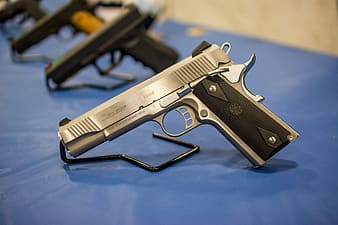 Silver and black 45 caliber pistol on top of blue surface