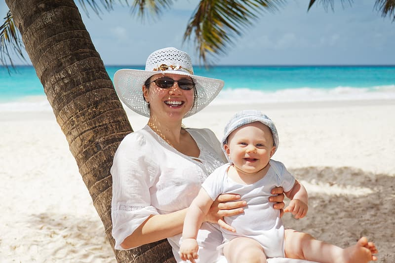 Woman smiling wearing sun hat holding a smiling baby sitting on her lap