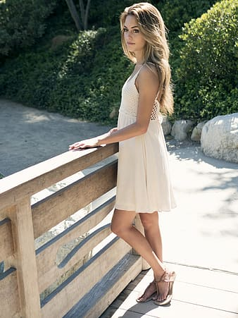 Woman wearing beige mini dress leaning on brown wooden railings during daytime