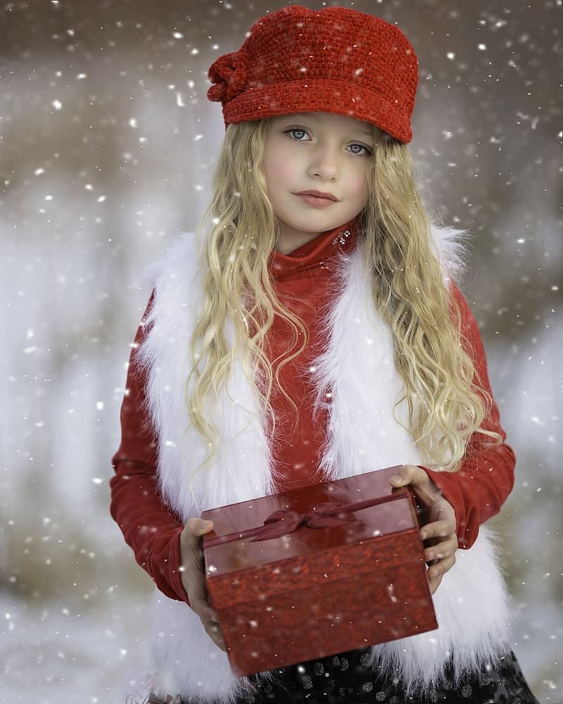 Shallow focus photography of girl holding red box