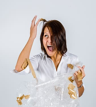 Woman standing near wall holding her hair with brown adhesive tape with her mouth open