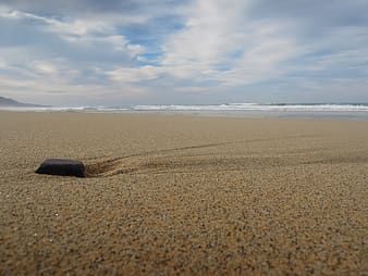Black rectangular device on brown sand near sea under white clouds and blue sky during daytime