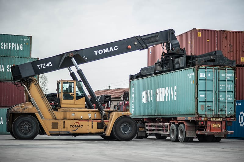 Yellow and black Tomac heavy equipment near container tank at daytime